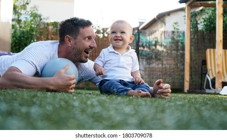 A cute baby and his smiling father playing on a grass with a ball