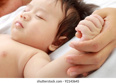 Cute baby holding mom's hand