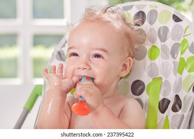 Cute baby holding spoon and eating watermelon