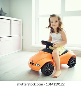 Cute baby at home in white room is sitting on toy car. The beautiful toddler girl driving a car. Baby with curly hair is looking to camera.
