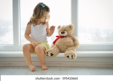Cute baby at home in white room is sitting near window. The beautiful toddler girl with teddy bear. Baby with curly hair is looking to toy.