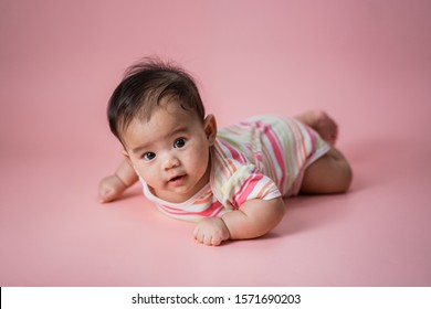 cute baby laying on her belly looking at camera