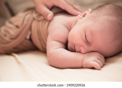 Cute baby lies on blanket. New born baby smilies happy in a dream and try try raise head