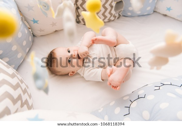 Cute baby lies in a white round bed. Light nursery for young children.  Toys for infant cot. Smiling child playing with mobile of felt and chewing his feet in sunny bedroom.