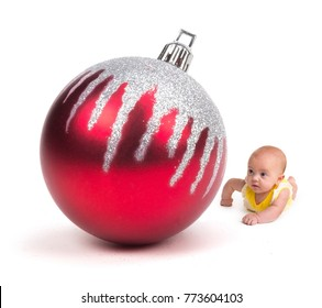 Cute Baby looking at a Huge Christmas Ornament on white