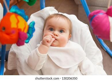 cute baby looking at the toys and sucks his thumb