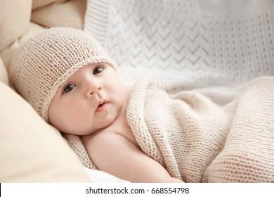 Cute baby lying in armchair