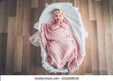 Cute baby lying in the basket, top view.