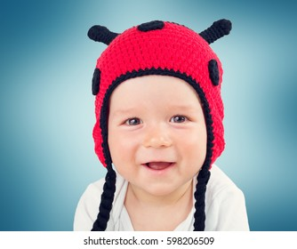 Cute baby lying in the bed on white blanket in knitted ladybug hat. Pretty little boy
