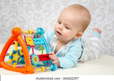 Cute baby lying on belly  on soft surface and intently playing with her colorful toys. Close up portrait