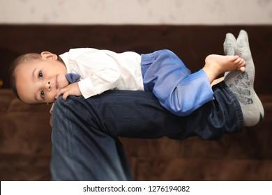 Cute baby lying on dady's legs