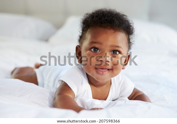 Cute Baby Lying On Tummy In Parent's Bed