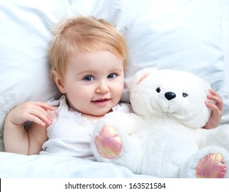 cute baby lying in white bed and holding a teddy bear toy