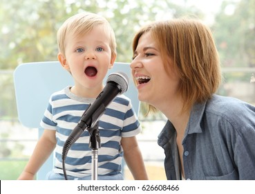 Cute baby with mother and microphone at home