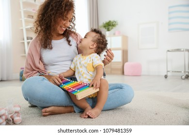 Cute baby and mother playing on floor at home