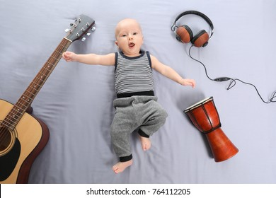 Cute baby with musical instruments and headphones on light background