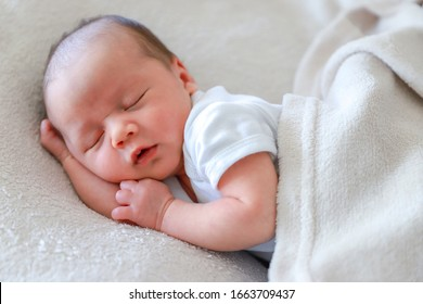 Cute baby newborn napping on bed with blanket at home.little mixed race Asian-German infant boy about 2weeks old day sleeping.