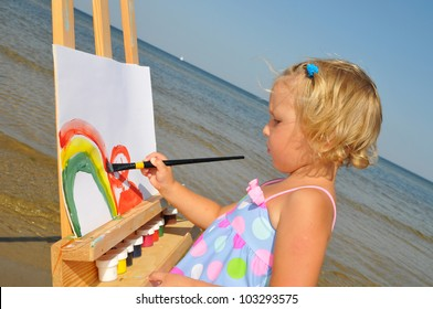 The cute baby painting brush watercolors portrait on a easel