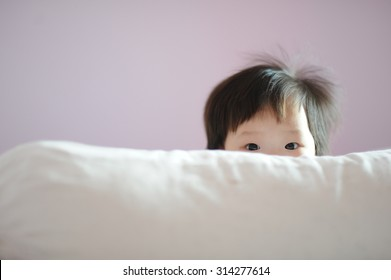 Cute baby peeking from of pillow on bed