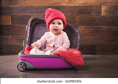 Cute baby in pink travel bag on wooden background