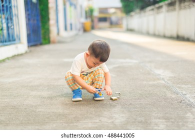 The cute baby is playing alone on street. he like it. but the parent should be careful because it may have some car crash him.