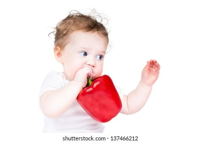 Cute baby playing with a big red paprika
