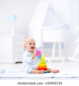 Cute baby playing with colorful rainbow toy pyramid sitting on play mat in white sunny bedroom. Toys for little kids. Interior for little boy nursery. Child with educational toy. Early development