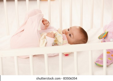 Cute baby playing with feet in baby crib, holding toy.?