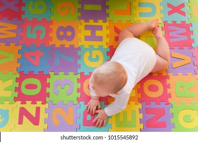 Cute baby playing on tummy on alphabet mats.