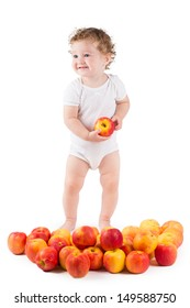 Cute baby playing with red apples, standing, white background