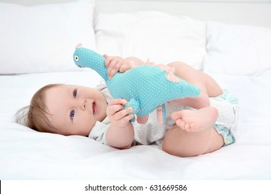 Cute baby playing with toy dinosaur on bed