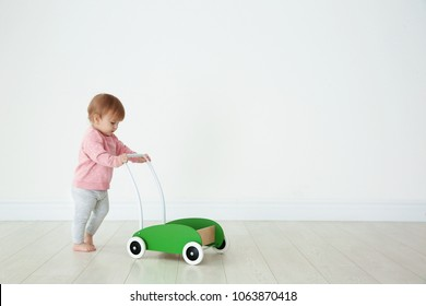Cute baby playing with toy walker, indoors