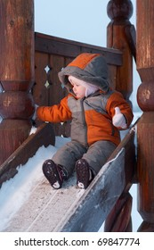 cute baby prepare to slide down the slides for children in winter