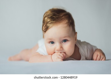 Cute baby putting hands in mouth and sucking fingers