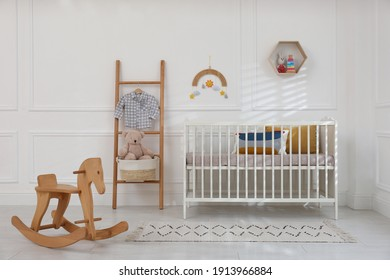Cute baby room interior with comfortable crib and wooden rocking horse