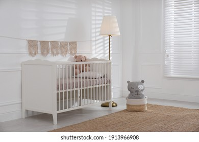 Cute baby room interior with comfortable crib and teddy bear