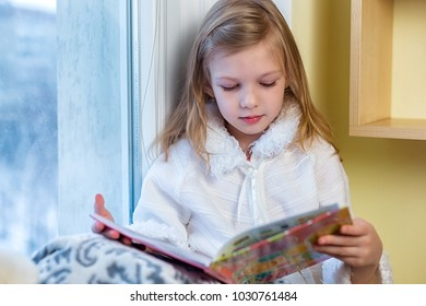 A cute baby in the room sits at the window in the winter and reads a book