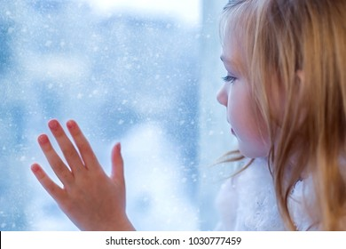 A cute baby in the room sits at the window in the winter