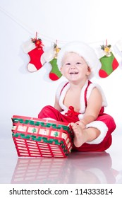 Cute baby Santa Claus with garlands and Christmas basket