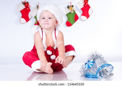 Cute baby Santa Claus with garlands of Christmas bootee