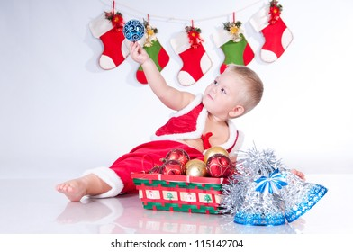 Cute baby Santa Claus with garlands and a basket of Christmas toys