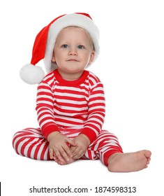 Cute baby in Santa hat and Christmas pajamas sitting on white background