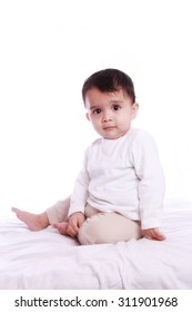 Cute baby  seating calmly , photographed against white background