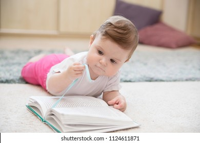A cute baby sits on the carpet on the floor reading a book. Homeschooling, early  education and early development concept