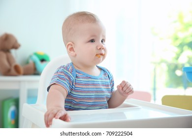Cute baby sitting in kitchen