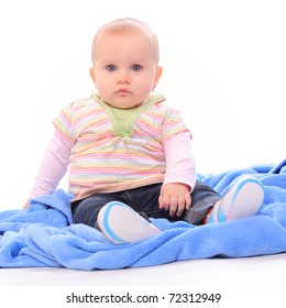 Cute baby sitting on blue towel.