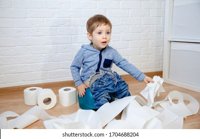 Cute baby sitting on chamber pot with toilet paper roll