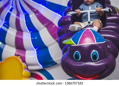 Cute baby sitting on a clud toy at playground