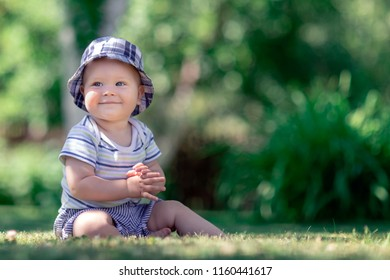 Cute baby sitting on the grass in the garden and applaud