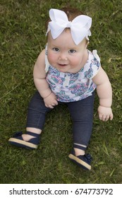 A cute baby sitting on the grass looking up, with a big smile.